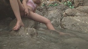 Freaky Alice rubbing against a rock to get her beaver wet
